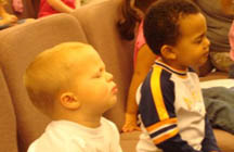 Toddlers praying in Christian preschool program